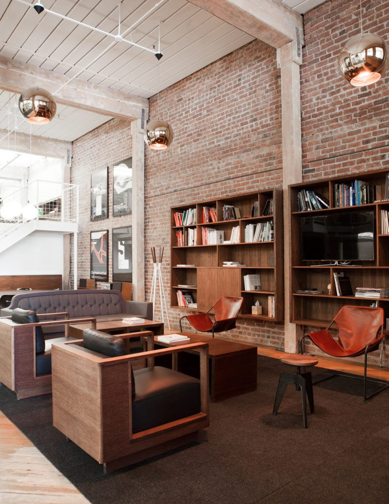 light-filled seating area in front of an exposed brick wall and book shelf // Method Office by Sky Lanigan Studios for Medium Plenty