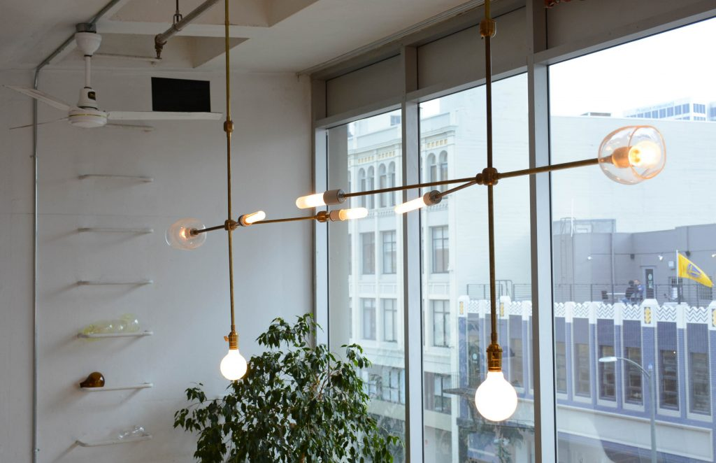 two custom lighting fixtures with raw brass and glass shades // Lighting by Sky Lanigan