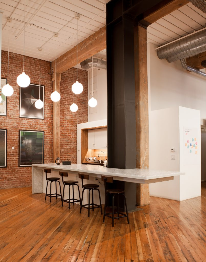 seating area around a black support beam with exposed brick wall // Method Office by Sky Lanigan Studios for Medium Plenty