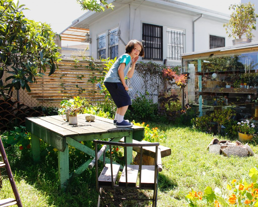 backyard with a child standing on an old wooden table // Casa Nueva by Sky Lanigan