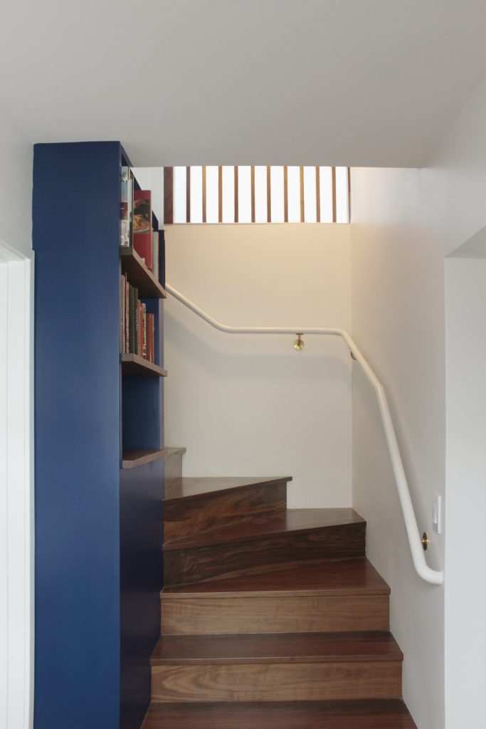 stairway with dark blue cabinet and light-filled slats // Cambridge by Sky Lanigan Studios